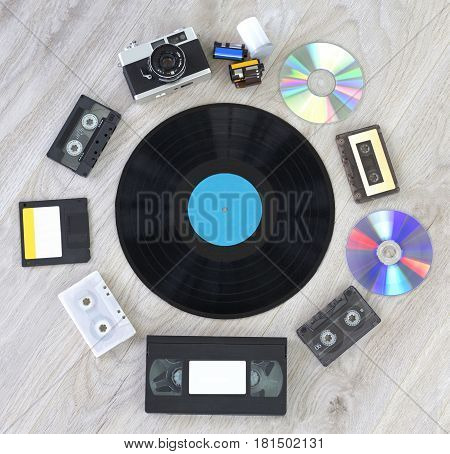 Various retro things. Camera, film, vinyl record disc, audio cassette, video cassette, floppy disc and CD close up image