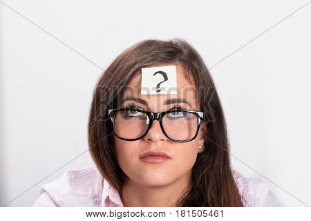 Woman Looking Up Over The Sticky Note With Question Mark On Her Forehead