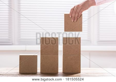 Woman's Hand Holding A Block To Complete Growth Bar Graph On Desk