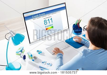 Close-up Of A Businesswoman Checking Credit Score On Computer At Workplace
