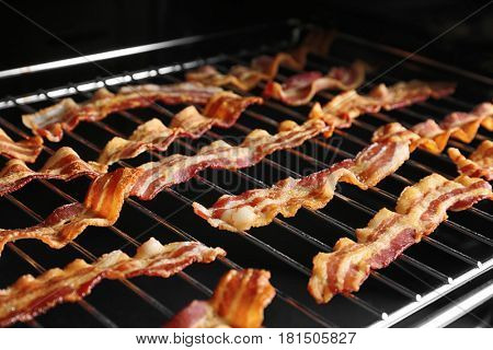 Grill with strips of bacon cooking in oven