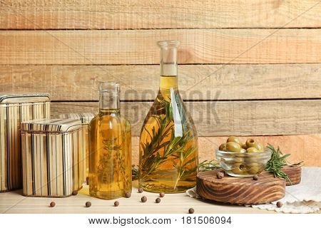 Olive oil with spices on wooden background