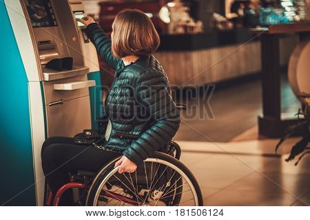 Physically challenged woman near ATM .