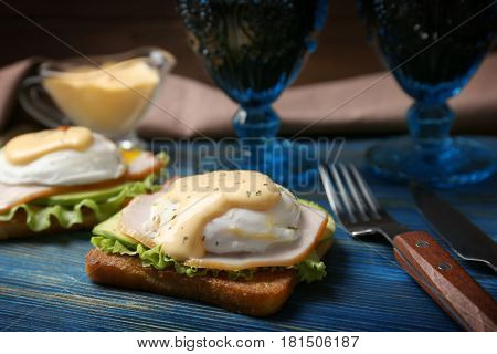Tasty eggs Benedict served on wooden board
