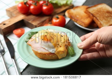 Female hand putting plate with tasty egg Benedict on table