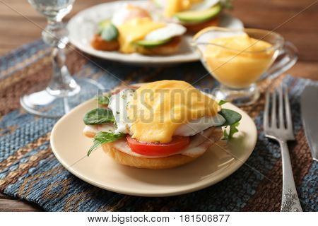 Plate with tasty egg Benedict on table