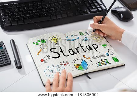 Close-up Of A Businesswoman Drawing Start Up Chart On Notebook Over Desk