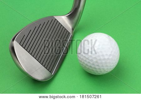 Golf club and ball on green background .
