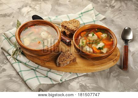 Crock pots with chicken soup on wooden board