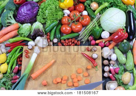 Fresh colorful vegetables with chopping board close up image