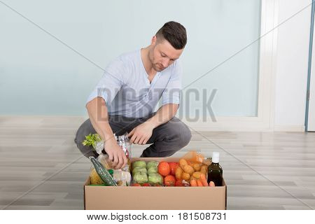 Young Man Checking The Groceries In The Box At Home
