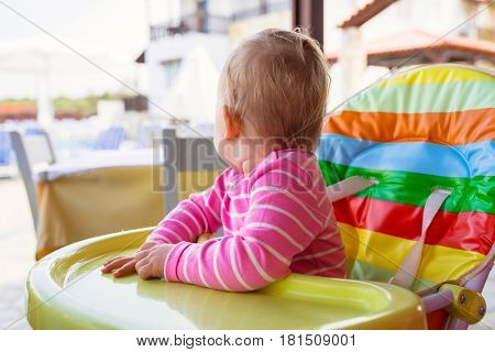 Little baby girl eating lunch on the high chair