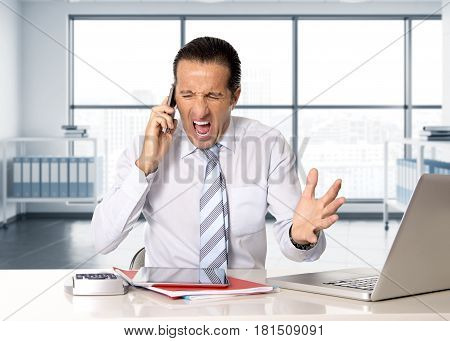 angry senior businessman in stress working and talking on mobile phone at computer desk looking desperate and worried for financial crisis at modern office in business district