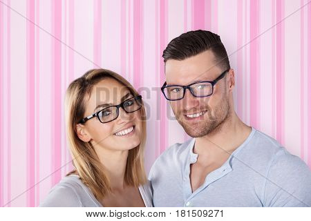 Portrait Of A Happy Young Couple With Eye Glasses Against The Wallpaper