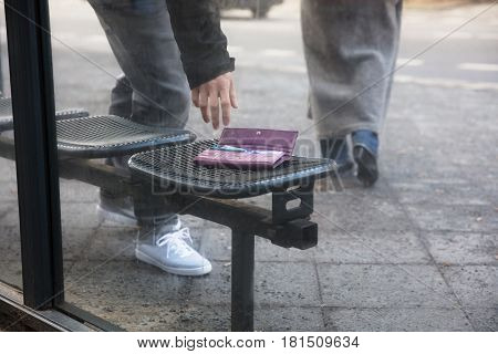 Close Of A Man Picking Up A Lost Purse On Bench At Street