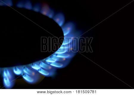 Natural gas blue flames on black background .