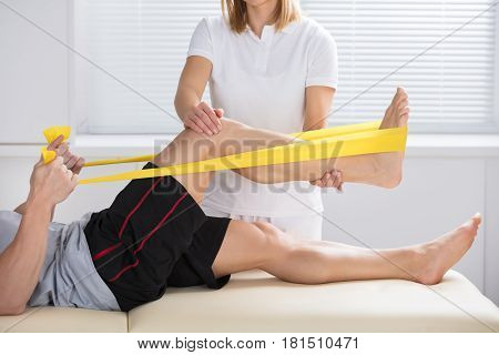 Close-up Of A Female Physiotherapist Giving Treatment With Exercise Band