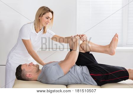 Female Physiotherapist Giving Knee Exercise To A Man In A Clinic