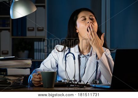Doctor Sitting At Desk And Yawning In Hospital