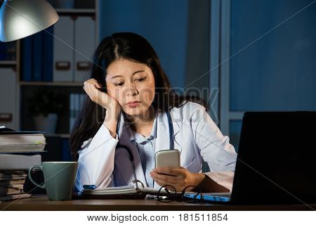 Female Practitioner Working In Office Using Smartphone