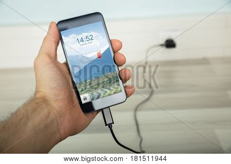 Close-up Of A Person Charging His Mobilephone Using Charger