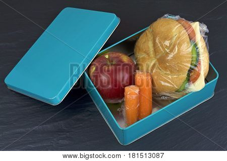 Healthy lunch box, cheese sandwich, apple and carrots close up image