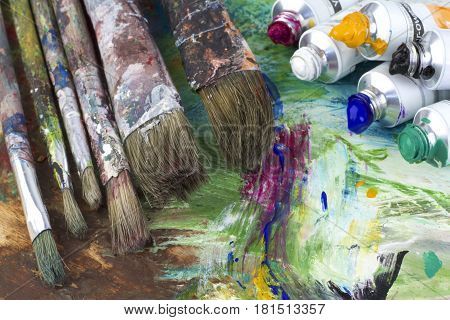 Paint colors and brushes on artist palette close up image
