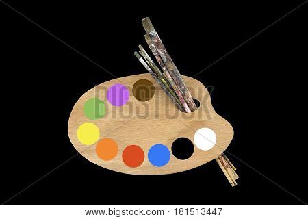 Paint brushes, colors and artist palette on black background
