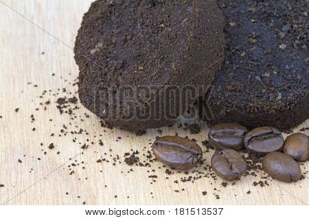 Used coffee grounds after espresso machine and coffee beans close up image