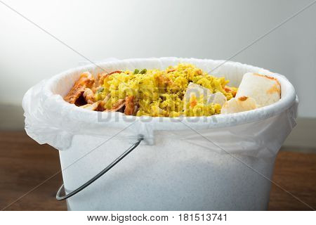 Close-up Of White Trash Bin Covered With Leftover Food