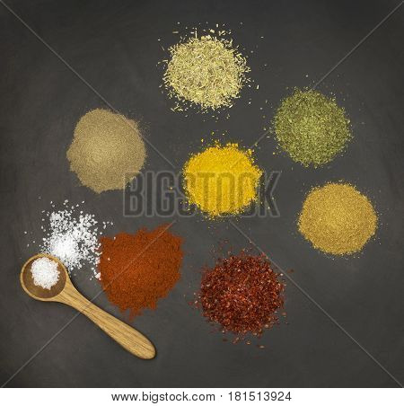 Various spices on black stone surface close up image