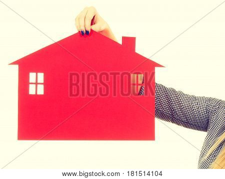 Ownership property real estate concept. Female hand holding red paper house symbol. New flat apartment. Toned image