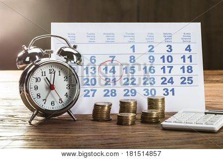 Tax Time On Alarm Clock With Coins Calculator And Calendar Over The Wooden Table