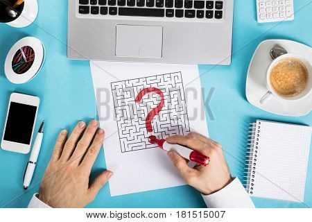 Elevated View Of A Businessman Drawing Labyrinth Maze On Paper With Office Supplies At Workplace