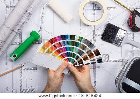 Architect Holding Color Guide Swatch On Blueprints With Paint Roller And Paint Brush