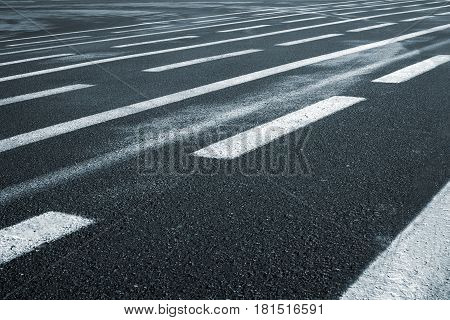 Lines on wet wide asphalt road perspective view. Texture and background