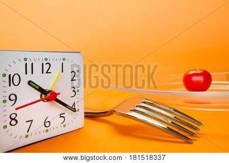 Alarm clock fork and small cherry tomato on abstract orange background. Diet and lunch time concept