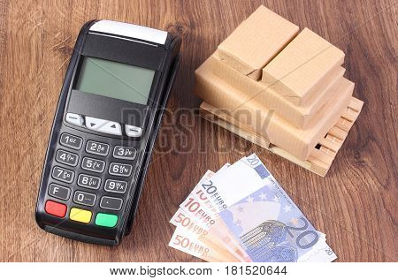 Payment Terminal, Currencies Euro And Wrapped Boxes On Wooden Pallet, Concept Of Paying For Products
