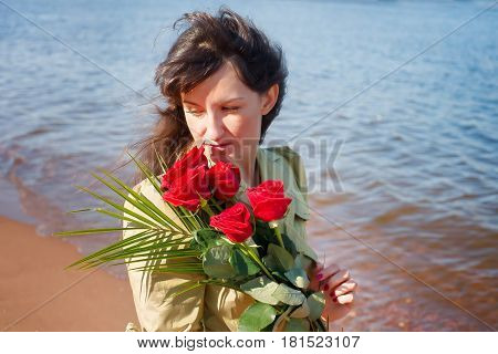 Dreamy Woman with red roses against the sea at sunny day. Brunette in a demi-season looking outside. Dating romance and memories theme poster