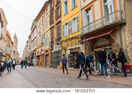Toulouse France, October 25, 2016; street scene with group young men with bicycles using thier portable dvices people walking and in cafes in street with shops and signage