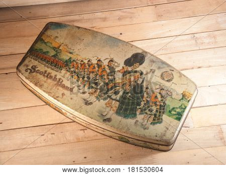 Thailand - April 09 2017 : An streel case of biscuits or cookie Scotish Band. An old case is on wooden.