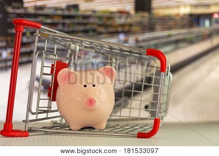Pink piggy bank pig standing inside mini shopping push cart with blurred supermarket background