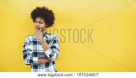 Pensive beautiful black teenage girl in checkered shirt with curly afro hair on yellow background thoughtful biracial female looking aside with copy space for your advertising message