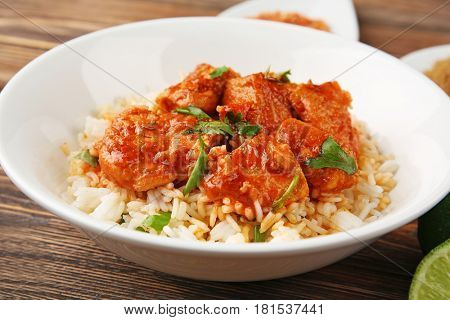 Plate with tasty chicken tikka masala and rice, closeup