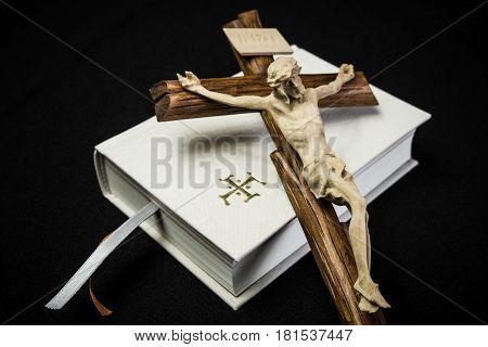 White prayer book and brown cross on black backround