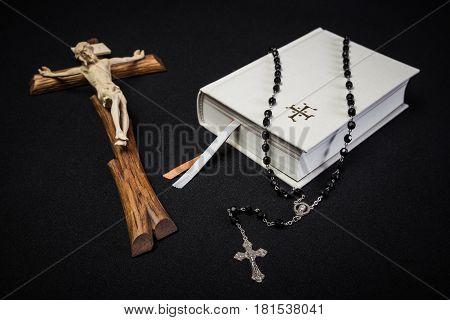 White prayer book rosary and Jesus on cross