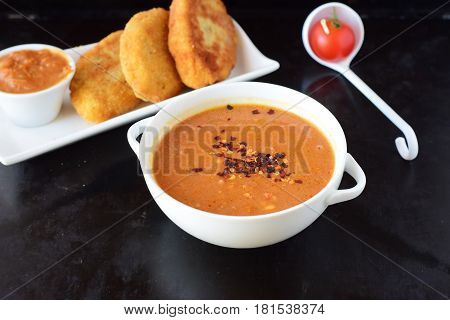 Tomato gravy for meatballs, pasta in a white bowl with potato patties on a black abstract background. Healthy food concept