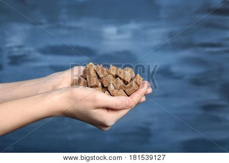 Female hands with brown refined sugar on color textured wall background