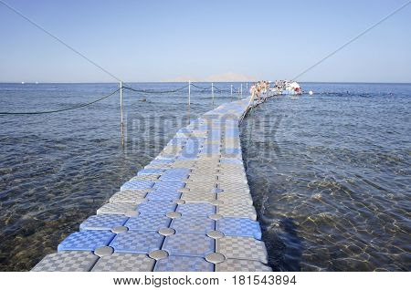 Plastic pier in the sea. People go to swim in the Red sea