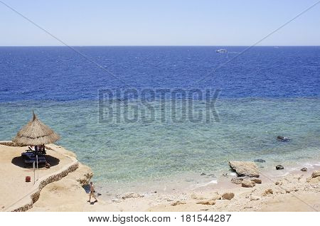 Shore of the red sea and a beach umbrella